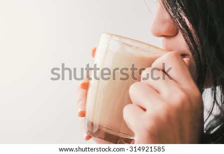 Close up woman drinking hot latte coffee at cafe - stock photo