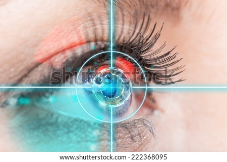 Close-up woman eye with laser medicine, technology concept. - stock photo