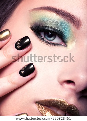 Close-up woman face with green eye make-up. - stock photo