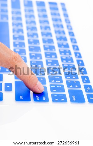 Close up woman finger on enter button blue Thai keyboard cover - stock photo