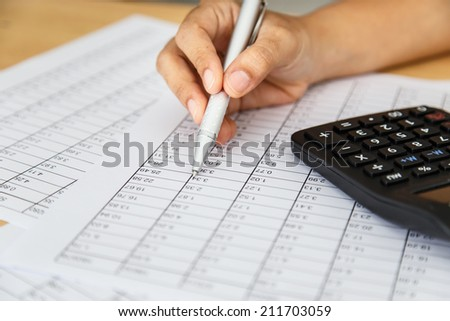 Close up woman hand holding pen on spreadsheet