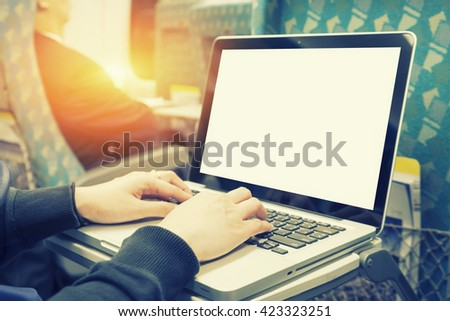 Close-up woman hands typing on a laptop keyboard in the train,sitting next to the window and looking at computer screen. Concepts of travel and lifestyle.,selective focus,vintage color - stock photo