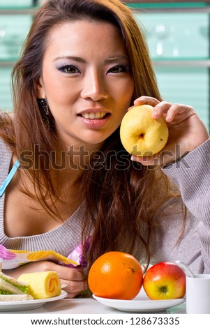 Close up woman holding fruit  in the kitchen - stock photo