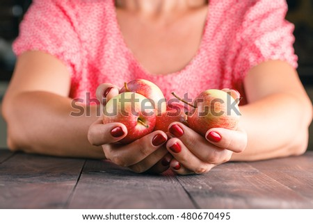 Close up woman holding red apples in hand