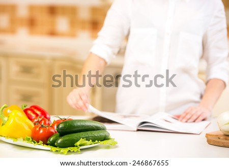 Close-up woman is reading cookbook in the kitchen, she is looking for recipe. - stock photo