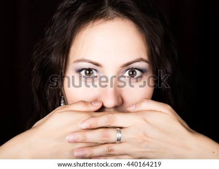 Close-up woman looks straight into the camera on a black background. She covered her mouth with her hand. expresses different emotions - stock photo