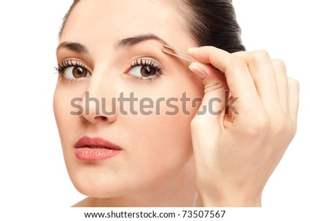 close up,  woman plucking her eyebrows with tweezers, isolated on white - stock photo