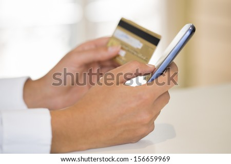 Close-up woman's hands holding a credit card and using cell phone for online shopping - stock photo