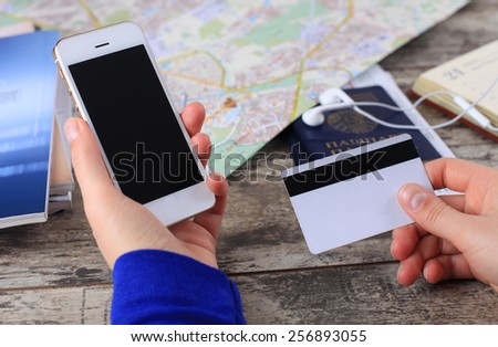 Close-up woman's hands holding a credit card and using cell phone for online tour booking on wooden table  - stock photo