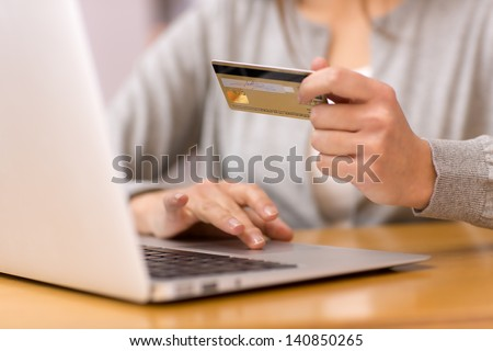 Close-up woman's hands holding a credit card and using computer keyboard for online shopping - stock photo