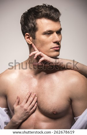 Close-up. Woman's hands on a sexy man's torso on a white background.