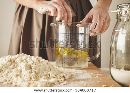 Close up woman twist spoon in measure cup with olive oil and water to prepare dough for pasta or ravioli - stock photo