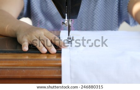 Close up woman working with sewing machine. - stock photo