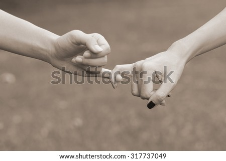 close up women hands making a pinkie for trust:swear and promise in relationship : selective focus on pinkie:image in sepia tone color styles.happy family and friends concept.international women's day - stock photo