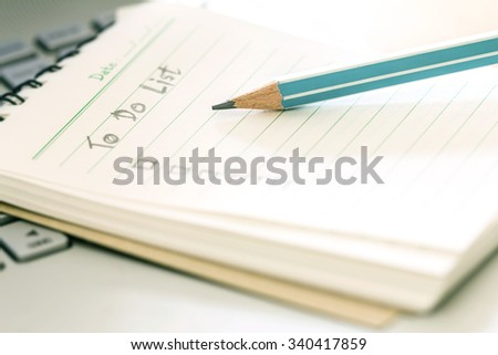 close up wooden pencil on Handwritten to do list plan in a  small note book - stock photo