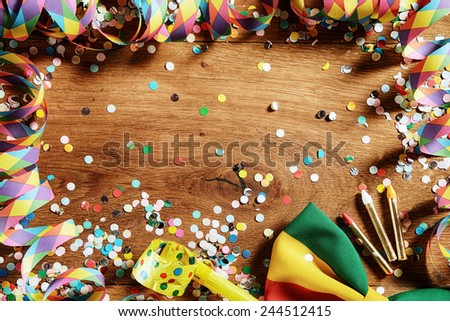 Close up Wooden Table with Festival Props - Confetti, Paper Streamers, Whistle, Ribbon and Pencil. Emphasizing Copy Space. - stock photo