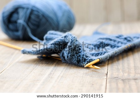 Close up wool dark blue knitting gold needle on grunge wood - stock photo