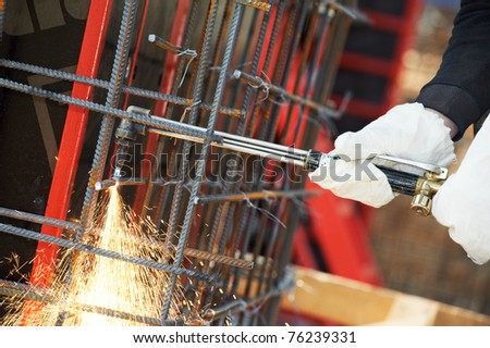 close-up worker hands in protective gloves cutting concrete reinforcing metal rods at construction site by gas flame - stock photo