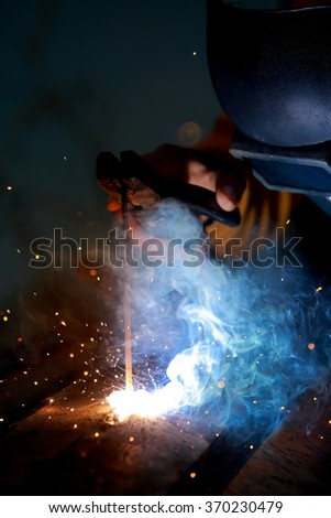 Close-up worker with protective mask welding metal.