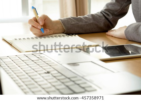 close up working woman writing on paper and typing on laptop computer in office room