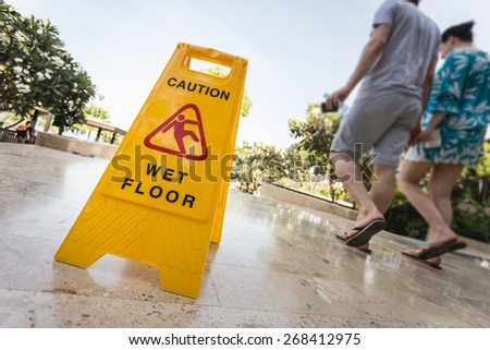 Close up yellow caution sign and blur of paeple walking on the walkway - stock photo