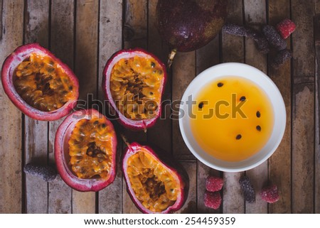 Close up yellow color passion fruit pulp and seed in small ceramic bowl isolated on BROWN board, andied fruit, plate with jam - stock photo