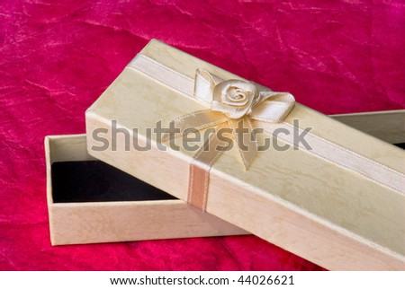 Close up: yellow gift box on red paper background