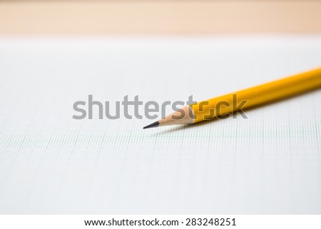 close-up yellow pencil on graph paper background - stock photo