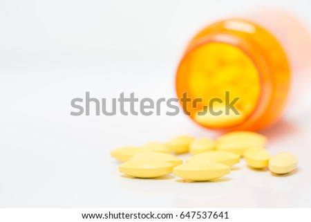 close up,Yellow pills In orange packaging , White background