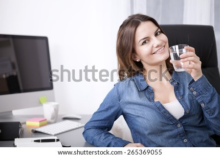 Close up Young Adult Office Woman Relaxing on her Chair While Holding a Glass of Water and Looking at the Camera. - stock photo