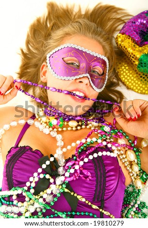 close up young and beautiful caucasian in colorful mardi gras dress holding a lot of beads lying on the floor - stock photo