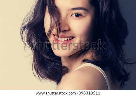 Close up young Asian woman with smiley face, grunge vintage style. - stock photo
