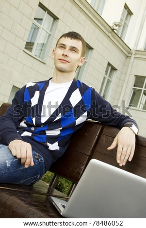Close-up young attractive student studies on a laptop in a college campus. Sitting on the stairs of the building - stock photo