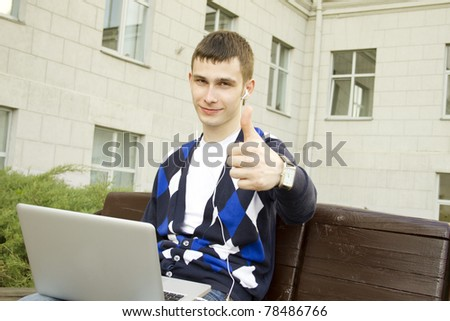Close-up young attractive student studies on a laptop in a college campus. Sitting on the stairs of the building. Thumbs up - stock photo