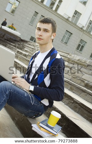 Close-up young attractive student studies on a with books and laptop in a college campus. Sitting on the stairs of the building - stock photo