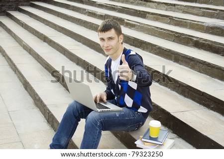 Close-up young attractive student studies on a with books and laptop in a college campus. Sitting on the stairs of the building. Thumb up - stock photo