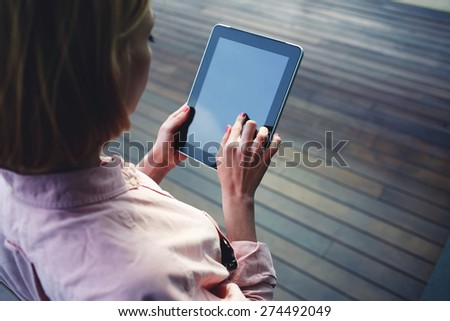 Close up young blonde female student using touch pad against wooden background, freelancer girl working on her digital tablet with big copy space,hipster woman browsing with touchscreen device, filter - stock photo