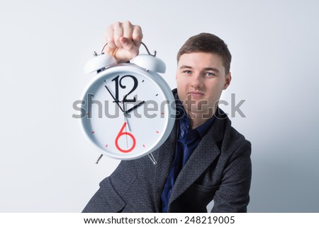Close up Young Businessman Holding Alarm Clock While Looking at the Camera, Isolated on White - stock photo