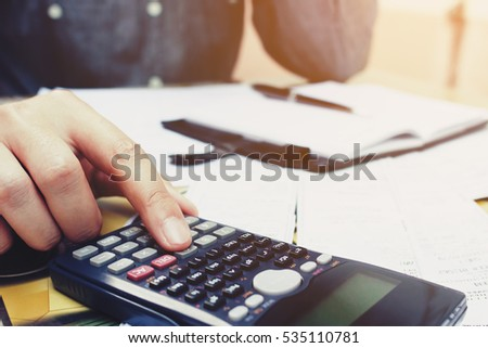 Close up young businessman using calculator and writing make note in home office.