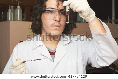 close up young chemist mixing colour reagent in lab - stock photo