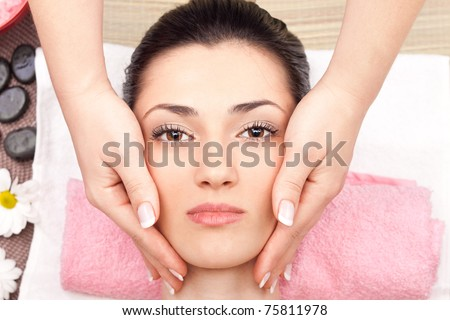 close up, young cute woman receiving a facial massage, top view - stock photo