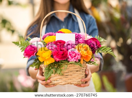 Close-up. Young female florist holding bouquet of flowers in shop. Focus on bouquet. - stock photo
