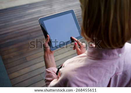 Close up young female student using blank screen touch pad against wooden background, freelancer girl working on digital tablet with copy space, hipster woman browsing with touchscreen device, filter - stock photo