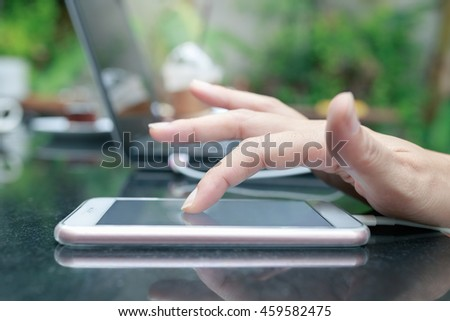 Close up young girl hand touching using smartphone connected with laptop computer to transfer data on desk and green nature background