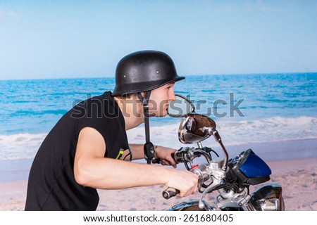Close up Young Handsome Man Riding a Motorcycle at the Beach with Black Helmet on a Tropical Climate. - stock photo