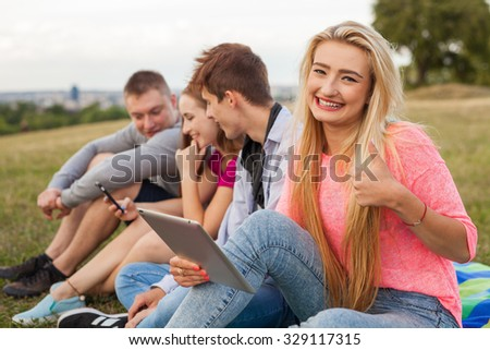 Close up. Young happy girl holding tablet pc in park - stock photo