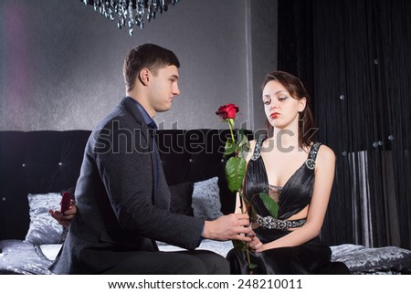 Close up Young Man Offering Rose Flower to Sad Girlfriend While Holding a Jewelry Box Behind his Back. Captured at the Bedroom. - stock photo