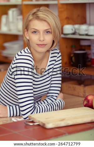 Close up Young Pretty Blond Woman in Black and White Stripe Shirt Leaning on the Table While Looking at the Camera. - stock photo