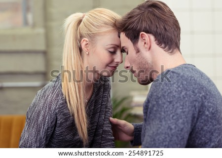 Close up Young Romantic Couple in Casual Gray Shirts Touching Their Foreheads with Eyes Close.