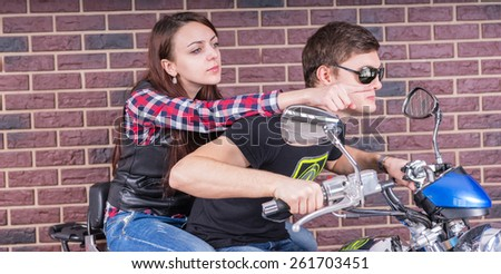 Close up Young White Couple in Casual Outfits Riding a Motorcycle on Brick Wall Background. - stock photo
